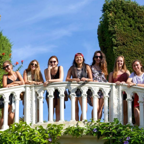 Semester students on a bridge in Nice, surrounded by greenery with blue sky and ancient columns behind.