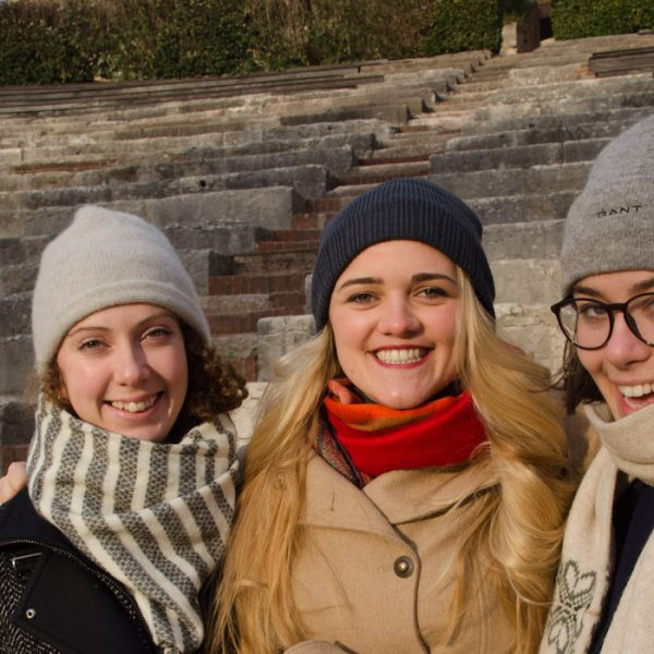 young tutors wrapped up in hats and scarves in the amphitheatre in Verona, Italy