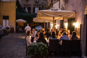 Early Summer gap year students eating at night outside at a restaurant in Italy