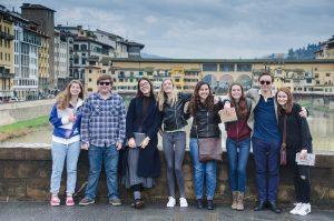 8 autumn gap year course students on a bridge in Florence with the Ponte Vecchio behind