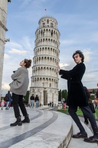 gap year course tutors, Marie and Liam, hold up the leaning tower of Pisa