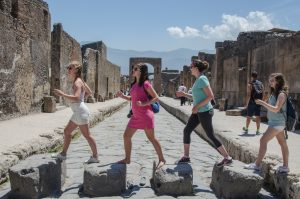 summer course students cross a road in Pompeii looking the Beatles Abbey Road album cover